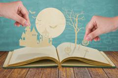 Paper cut of halloween on old book Stock Photos