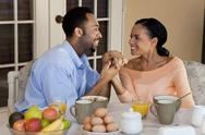 Happy african american couple holding hands at healthy breakfast Stock Photos