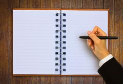 Hand writing in open paper on table Stock Illustration