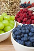 healthy breakfast blueberries, raspberries, strawberries, grapes and granola - stock photo