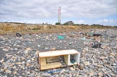 trashed fridge on the seashore next to a factory - stock photo
