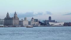 Mersey ferry crosses in front of liverpool skyline at dusk Stock Footage