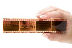 Holding a Filmstrip Isolated on a White Background Stock Photos