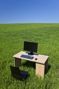 desk and computer in green field with blue sky - stock photo