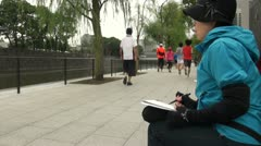 Water painting the Imperial Palace in Tokyo and morning runners Stock Footage