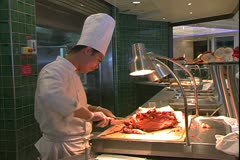 The Queen Mary 2, ocean liner, chef on buffet line carving a rib roast - stock footage