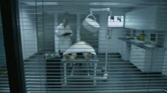 Dead body on an autopsy table being studied by the medical examiner - stock footage