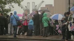 Tourists in the rain with flags watching Diamond Jubilee Boat Pageant Stock Footage