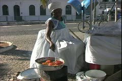 Salvador de Bahia, Brazil, old African woman frying plantains in skillet - stock footage