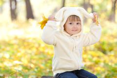 beautiful little girl in costume bunny in the autumn forest - stock photo