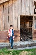 patriotic boy and old barn - stock photo