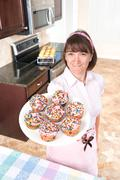 Homemaker holding plate of cupcakes Stock Photos