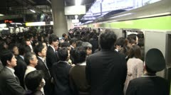 Rush hour Tokyo - passengers enter the carriage (handheld) - stock footage
