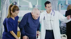 Multi ethnic medical team helping elderly patients on the hospital ward Stock Footage