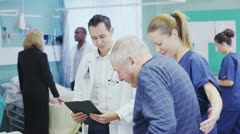 Multi ethnic medical team helping patients on the hospital ward - stock footage