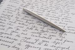 stainless steel pen laying on written page - stock photo