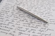 Stock Photo of stainless steel pen laying on written page