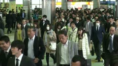 Tokyo train station during rush hour, crowds make their way to work Stock Footage