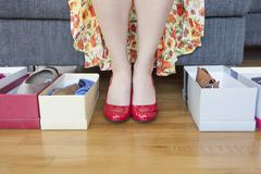 Woman's feet with shoe boxes on floor - stock photo