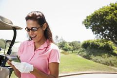 Woman keeping score during golf game Stock Photos