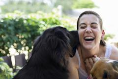 Hispanic woman playing with dogs Stock Photos