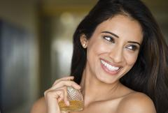 Stock Photo of Indian woman spraying perfume on neck
