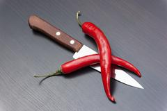 red chili peppers and knife on the kitchen table - stock photo