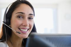 Caucasian businesswoman wearing headset at desk Stock Photos