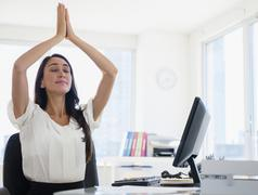 Caucasian businesswoman meditating at desk Stock Photos