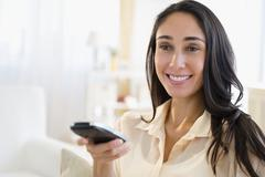 Caucasian woman watching television - stock photo