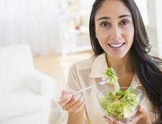 Caucasian woman eating salad - stock photo