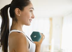 Caucasian woman lifting weights - stock photo
