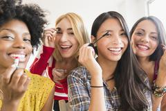 Smiling women applying make up - stock photo