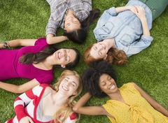 Smiling women laying in grass together Stock Photos