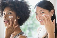 Smiling women applying moisturizer to cheeks Stock Photos