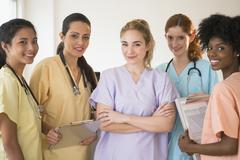 Nurses in colorful scrubs talking in hospital Stock Photos