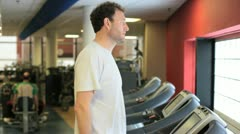 In a gym working out a middleage man is walking on a treadmill Stock Footage