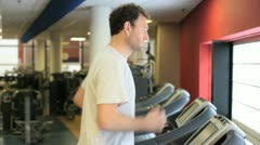 In a gym working out white man running on treadmill Stock Footage