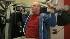 In a gym working out training biceps on a machine Stock Footage
