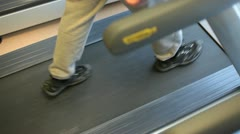 In a gym working out walking on a treadmill diagonal Stock Footage