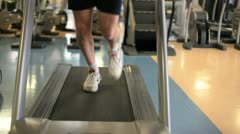 In a gym working out man running on a treadmill Stock Footage