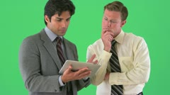 Businessman talking to colleague with a tablet on greenscreen - stock footage