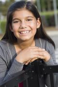 Hispanic girl leaning on metal railing Stock Photos