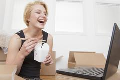 Caucasian woman eating take-out and looking at laptop Stock Photos