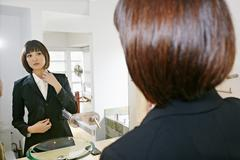 Mixed race businesswoman adjusting her collar in mirror Stock Photos