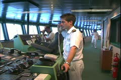 Queen Mary 2 ocean liner, the bridge, crewman at the helm on telephone Stock Footage