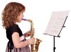 Pikkutyttö soittaa musiikkia saksofoni Kuvituskuvat