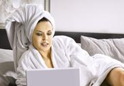 Lady with laptop on bed Stock Photos