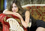 Rich woman on a red expensive sofa Stock Photos
