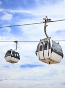 two cable car on a partly cloudy sky background - stock photo